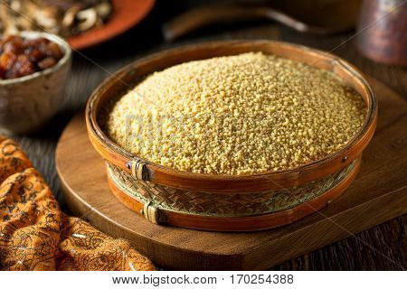 A bowl of raw organic couscous on a rustic background.