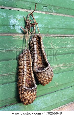 Old bast shoes (traditional russian footwear) on a green wooden background