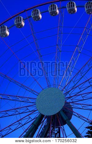Ferris wheel in amusement park against the background of the blue sky.