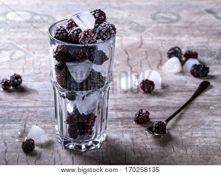 Glass tumbler with blackberries and ice on a gray background. Spoon the berries next
