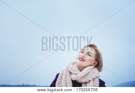 Young woman blonde who wears a big  pink bouffant scarf, day, outdoor . violetcoat