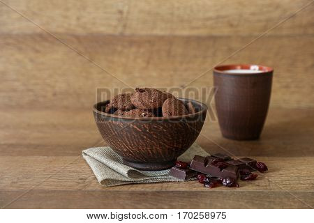 Natural chocolate cookies with cranberries and hazelnuts in the bowl near chocolate, cranberries, glass of milk on wooden background in rustic style. Horizontal.