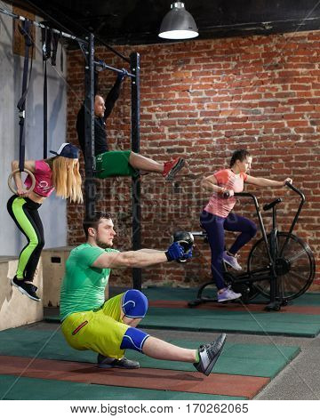 Two men and two women are training at the contemporary cross fit gym performing different exercises, pistol squats and push ups and leg rise