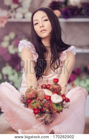 Beautiful girl in tender pink dress with flowers peonies in hands sitting on table against flower background in flower shop. Joyful asian female florist. Playful fashion model looking at camera.