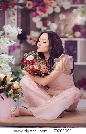 Beautiful girl in tender pink dress with bouquet flowers peonies in hands sitting on table against floral background in flower shop. Joyful asian female florist smells bunch of spring flowers.