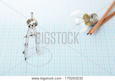 compass light bulb and pencils on millimeter paper abstract business concept
