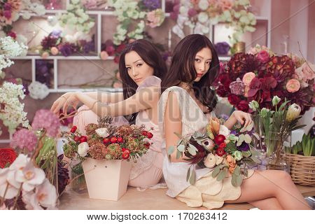 Fashion models in tender dresses posing and looking at camera. Beautiful asian florist girls making bouquet of flowers on table for sale against floral bokeh background in flower shop indoors. Two attractive asian females florists working in store.