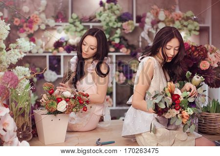 Beautiful asian florist girls making bouquet of flowers on table for sale against floral bokeh background in flower shop indoors. Two attractive asian females florists working in store. 2 playful fashion models in tender dresses posing playing with flower