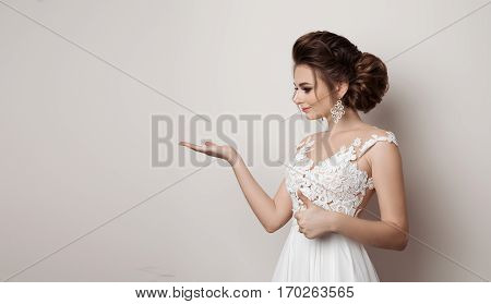 Portrait of brunette woman gesturing super sign by big finger and showing by hand to side holding something on hand. Woman wearing dress with elements of lace stylish haircut with big earrings.