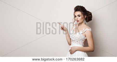Gorgeous bride in wedding dress shocked looking at camera and gesturing by finger at side. Brunette woman with stylish haircut posing at studio pointing by hand to side. Concept of beauty