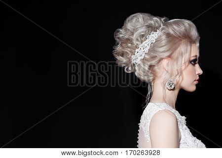Side view of gorgeous blonde in wedding dress with shiny earrings and accessories in hair. Stylish bride haircut of curly blonde hair. Pretty woman posing and turned away. Black studio background.