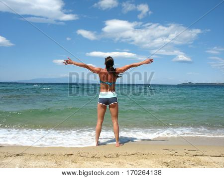 Beautiful young girl on the beach enjoys in a beautiful day