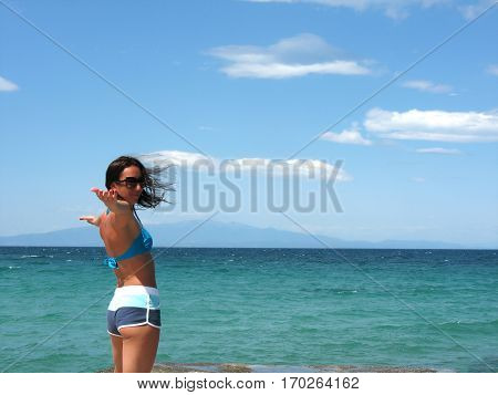 Beautiful young girl on the beach on a windy sunny day
