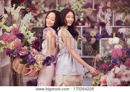 Beautiful asian florist girls holding bouquet and basket of flowers for sale against floral bokeh background in flower shop indoors. Two attractive asian females florists working in retail store. 2 playful fashion models in tender dresses posing smiling a
