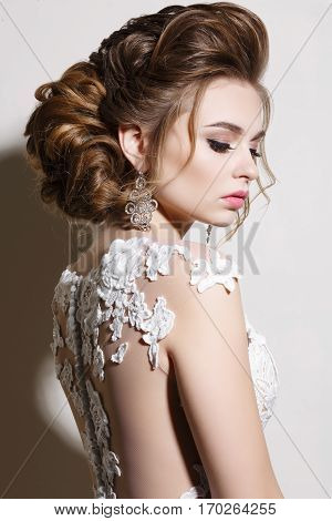 Gorgeous brunette girl posing at studio with cloded eyes looking down. Woman after beauty salon with stylish haircut and evening make up. Female wearing white dress and big earrings.