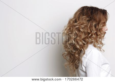 Gorgeous incognito woman after beauty salon wearing in white shirt posing at studio. White background. Side view of curly girl with curly volume haircut turned and looking away.