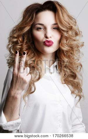 Emotional curly woman gesturing peace sign by fingers and making duck face. Girl with marsala lips in white shirt posing at camera and blowing air kiss at camera. Gray studio background.