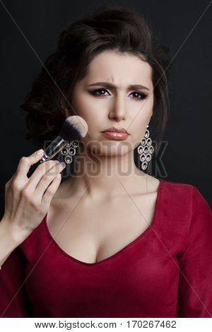 Portrait of capricious brunette woman emotionally posing at studio when incognito makeup artist making blush on cheekbone with brush. Unhappy girl in red dress with stylish haircut and big earrings.