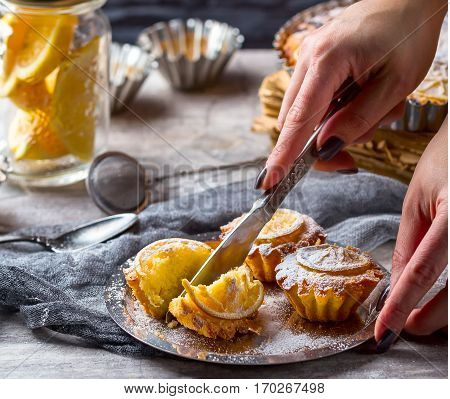 Lemon muffins on a metall plate. Hand cut the cake knife . lemon in a bowl in the background. Cakes sprinkled with powdered sugar