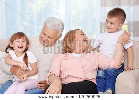 Happy grandparents with grandchildren sitting on couch
