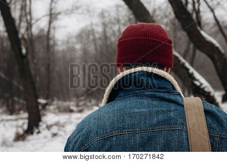 Stylish Hipster Traveler With Backpack In Red Hat Walking In Winter Snowy Forest. Wanderlust And Adv