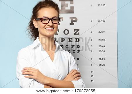 Young woman with spectacles near eyesight test chart in clinic