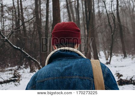 Stylish Hipster Traveler, Back View, Look Of Denim Jacket  Red Hat And Backpack On Background Of Sno