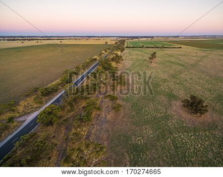 Rural Pastures And Meadows In Australia At Sunset Aerial View With Rural Road Passing Through.