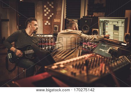 Sound engineer and guitarist recording song in boutique recording studio.
