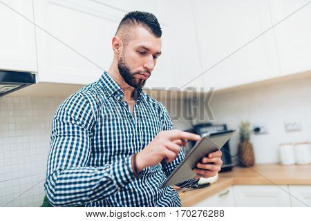Close Up Portrait Of Handsome, Attractive Man Looking Receipes On Internet. Man Using New Technology