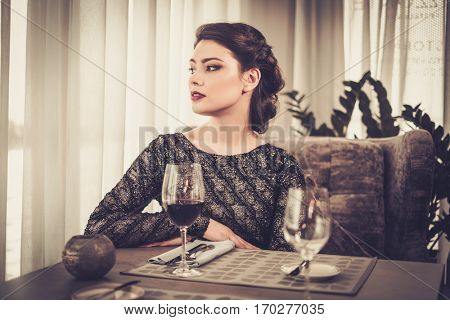Attractive sensual young lady with glass of wine in restaurant.