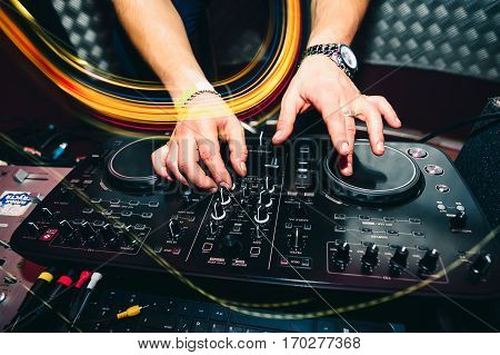 music remote for information and mixing music in a nightclub with a DJ hands close up