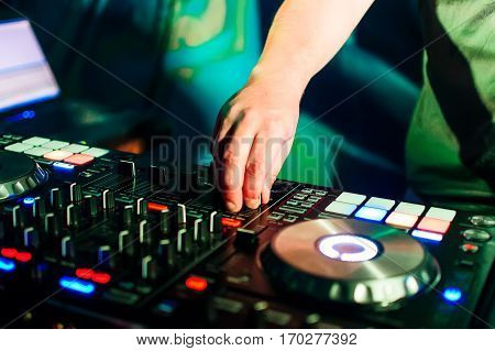 professional music equipment for mixing music in a nightclub with a hand of DJ