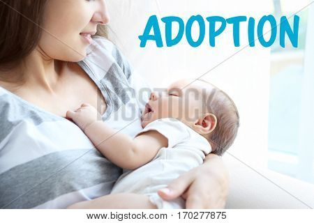 Adoption concept. Mother holding sleeping baby at home