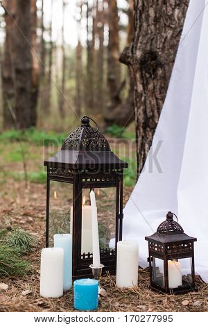 White and blue candles on candlesticks and in lanterns in forest near the wedding arch with white material