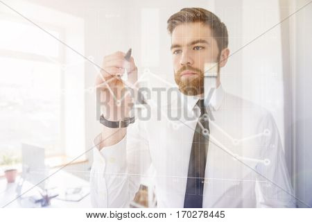 Confident business man drawing business strategy on virtual screen while standing in his office