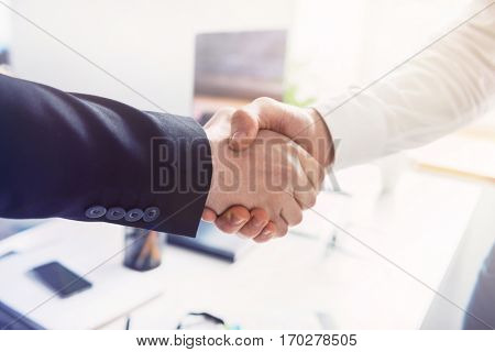 Close up of two successful businessmen shaking hands in the office