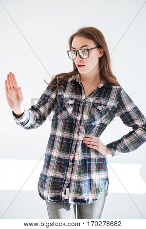 Serious young woman in glasses standing and showing stop gesture over white background