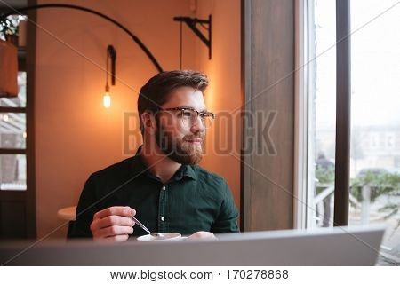 Image of handsome bearded young man wearing glasses sitting in cafe while drinking tea and using laptop.