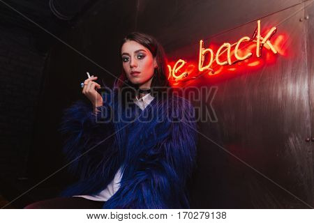 Photo of serious young woman standing with cigarette outdoors at night.