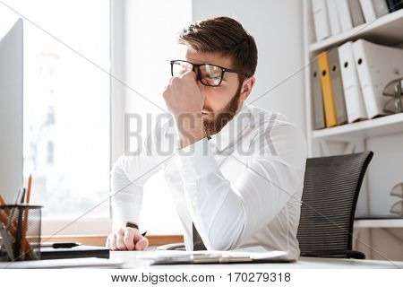 Photo of tired young businessman sitting in office while touching eyes.