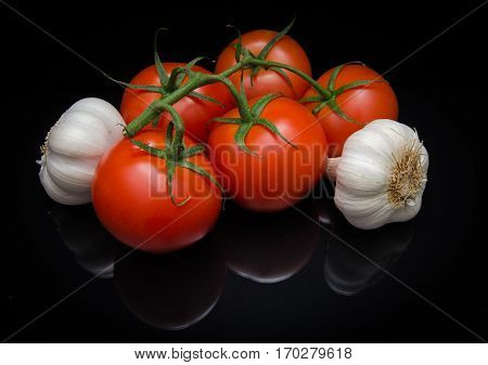 Red Vine Ripe Tomatoes with Garlic reflecting off an isolated black background. Ingredients for ketchup