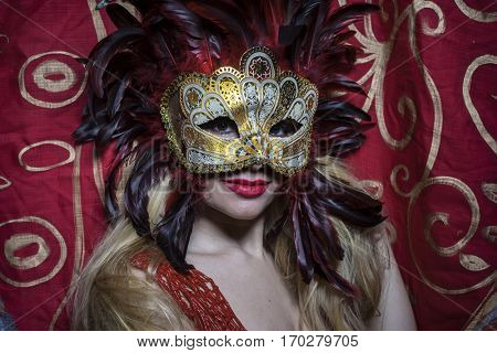 Smile, Beautiful blond woman with mysterious mask with red feathers. The background has floral motifs in garnet and gold