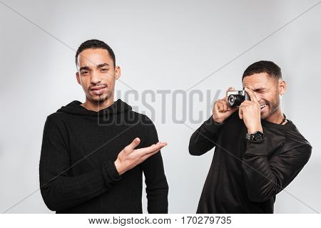 Picture of young african men photographer standing over white background and make a photo of his confused friend.