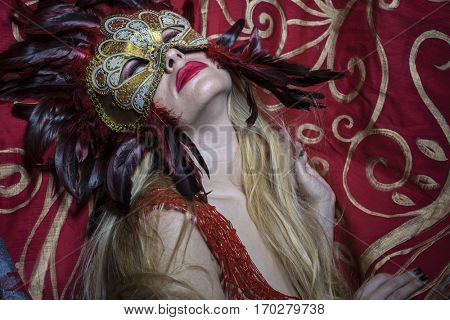 Beautiful blond woman with mysterious mask with red feathers. The background has floral motifs in garnet and gold