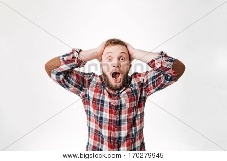 Surprised screaming Bearded man in shirt holding his head and looking at camera. Isolate white background