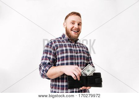 Happy Bearded man in shirt puts money in purse in studio. Isolated white background