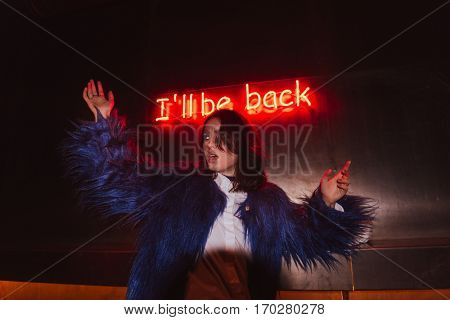 Scared young woman with raised hands over background with glowing inscription I'll be back