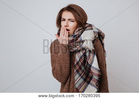Tired woman in sweater and scarf yawns in studio and looking at camera. Isolated gray background
