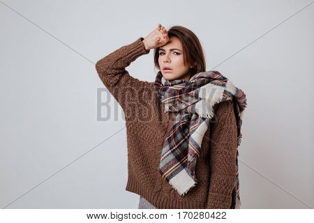 Sick woman in sweater and scarf touching her forehead and looking at camera